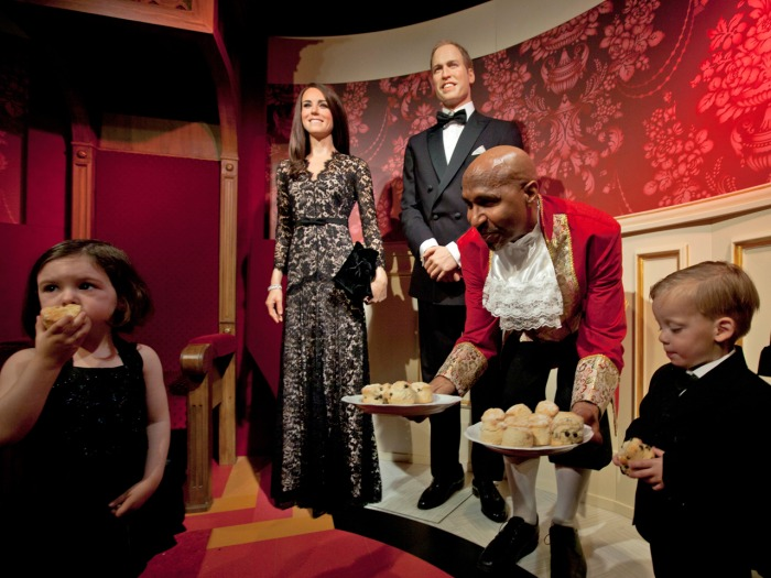 Child models eat scones as they pose with waxworks of Britain's Royal couple William and Catherine, the Duke and Duchess of Cambridge, at Madame Tussa...