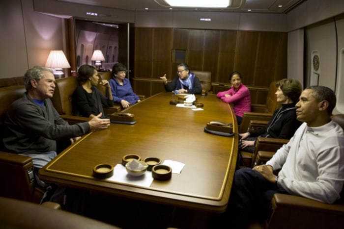 President Obama and President Bush talk as they get ready to have dinner aboard Air Force One with their wives and Valerie Jarrett, Tina Tchen and Sus...