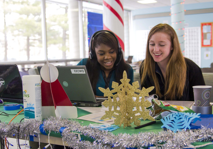 University of Illinois students Pauline Chitamdo, left, and Patti Grzyb sing to callers as part of the annual Dial-A-Carol program in Champaign, Ill. The student-run project is a hotline of sorts for people who prefer their holiday carols sung live by amateurs.
