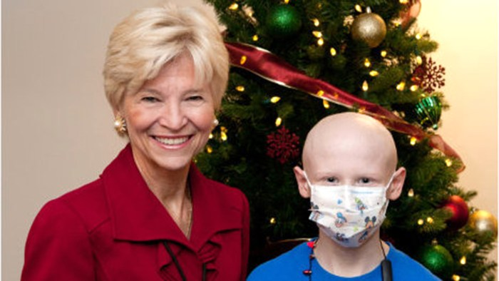 Owen Perry and Sandra Fenwick, president and CEO of Boston Children's Hospital, after Owen helped light a hospital Christmas tree.
