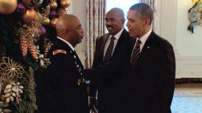 The president greets a member of the military as Steve Harvey looks on.