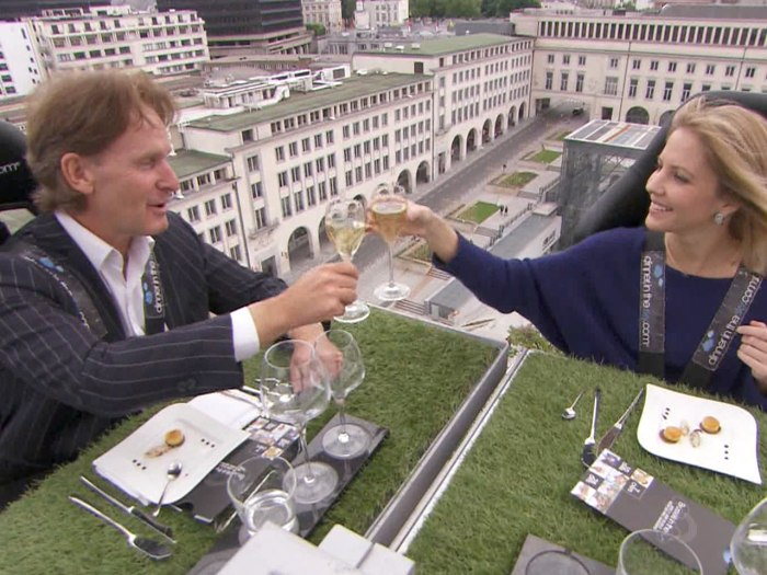 TODAY's Michelle Kosinski toasts a fellow diner while strapped into her seat high above Brussels.