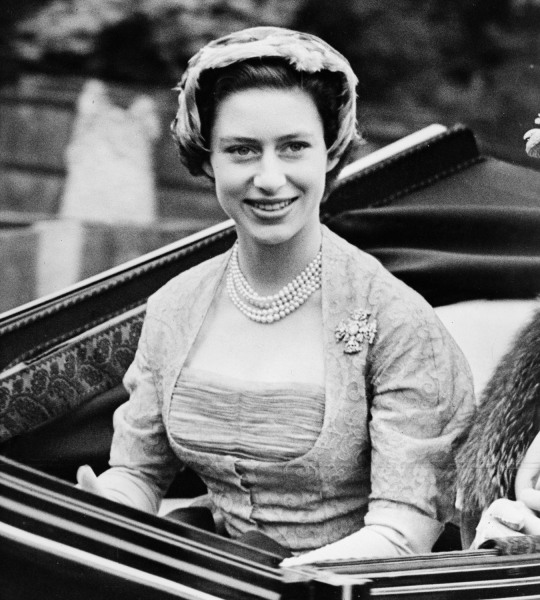 Princess Margaret wears a 1952 gray lace dress by Norman Hartnell. The boned fitted bodice is intricately constructed in layers of grey silk net with grey leaf-patterned lace underneath.