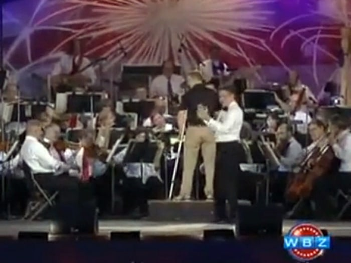 "Boston Pops conductor Keith Lockhart (in white) introduced Donohue as a ""the living embodiment of an everyday hero"" before he led a rendition of the Dropkick Murphys' ""I'm Shipping Up to Boston."""