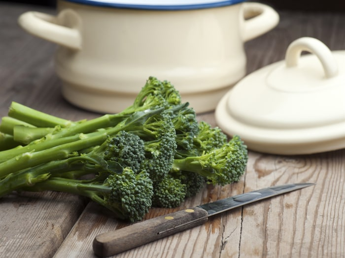 Fresh Broccoli Laid On A Wooden Kitchen Table With A Vegetable Knife and A Pan With Lid In The Background
