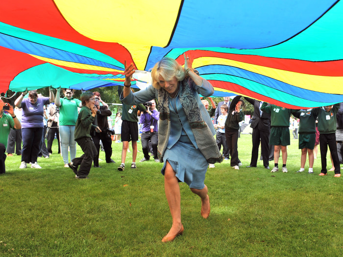 Image: Camilla runs under a brightly colored parachute during a youth rally on July 19, 2012 in Guernsey during a Diamond Jubilee visit to the Channel Islands with Prince Charles.