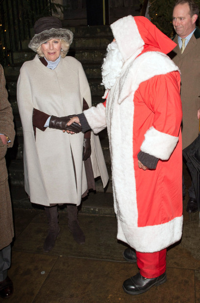 Image: Camilla meets Father Christmas and helps him switch on the Christmas lights on Dec. 7, 2012 in Tetbury, England.