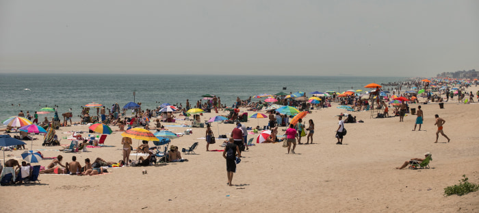 People flock to Rockaway Beach during a heat wave on July 17, 2013.