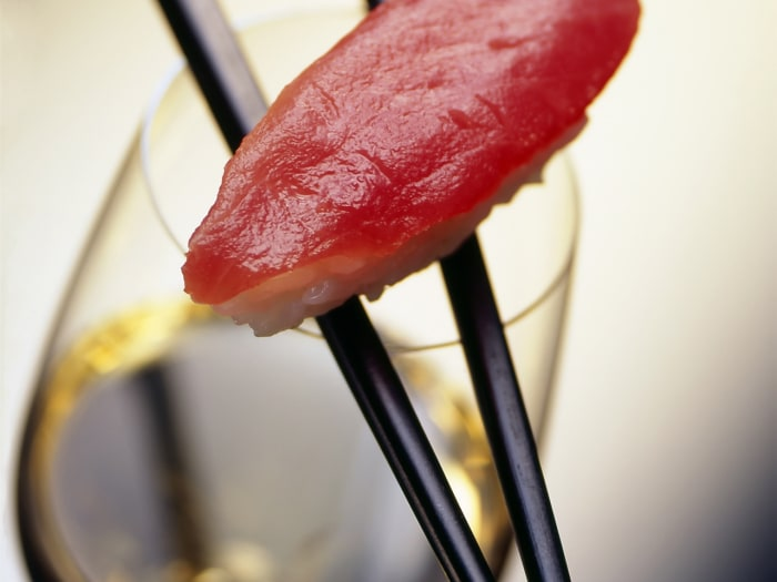 A piece of salmon and rice on two chopsticks laying on a glass of white wine