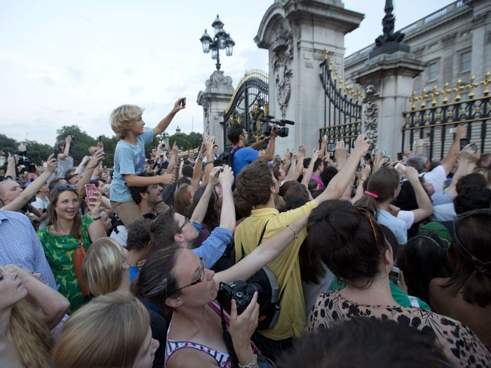Image: Crowds try to look at a notice formally announcing the birth of a son to Britain's Prince William and Catherine, Duchess of Cambridge, in the forecourt of Buckingham Palace in London on July 22, 2013.
