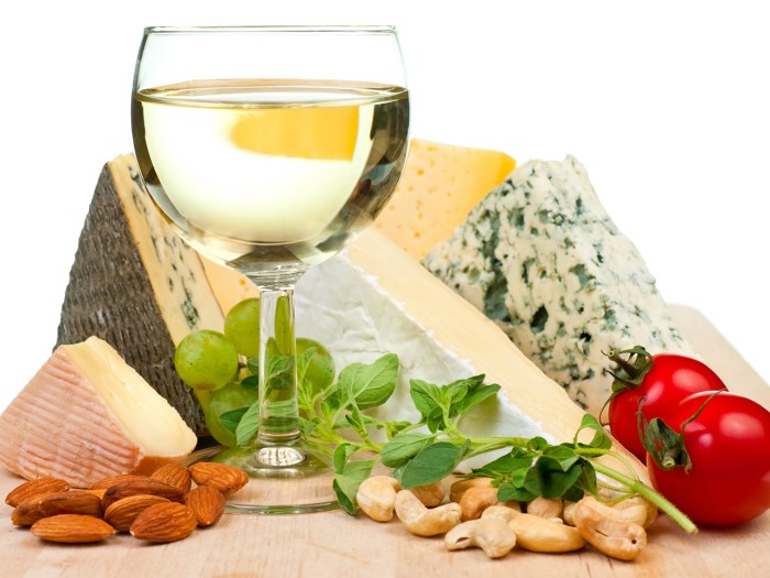 Glass of white wine with various types of cheese and garnishes
