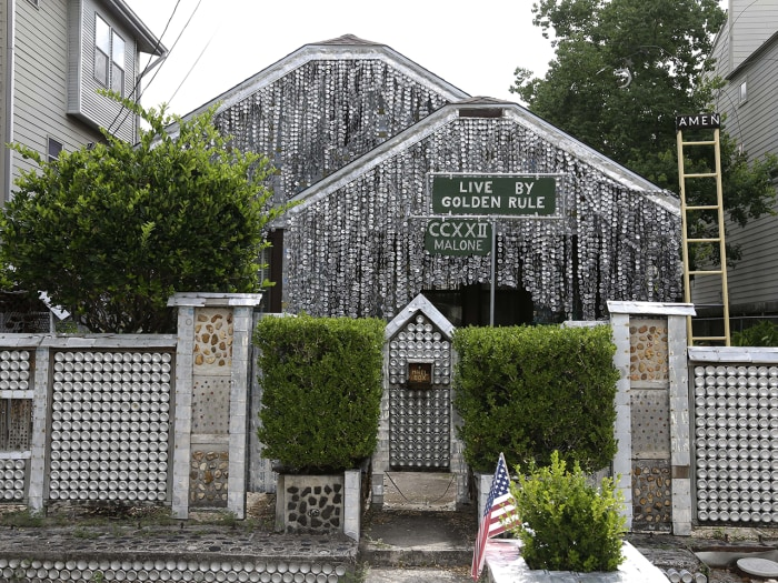 The beer can house, a Houston landmark, sits between newer homes Wednesday, July 10, 2013, in Houston. Former owner John Milkovisch covered the outsid...
