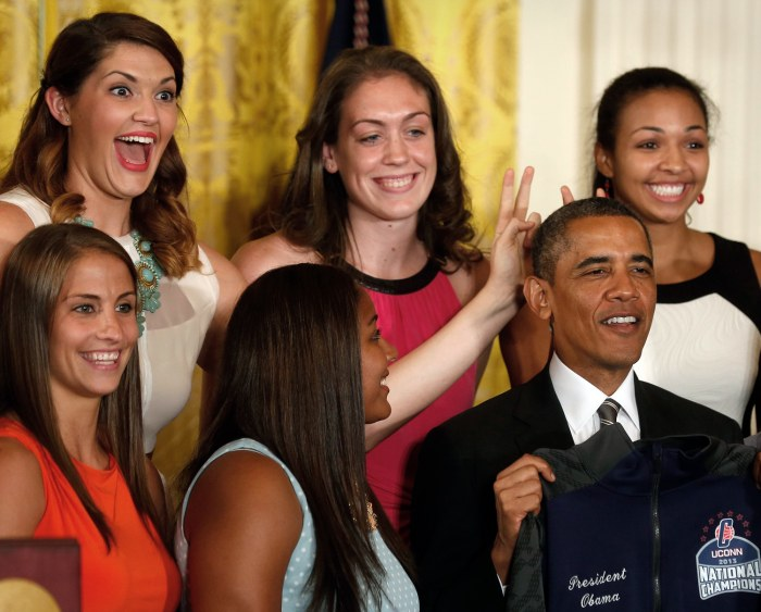 Image: Stefanie Dolson (top left), NCAA women's basketball 2013 national champions player from the University of Connecticut, puts bunny ears over U.S. Presi...
