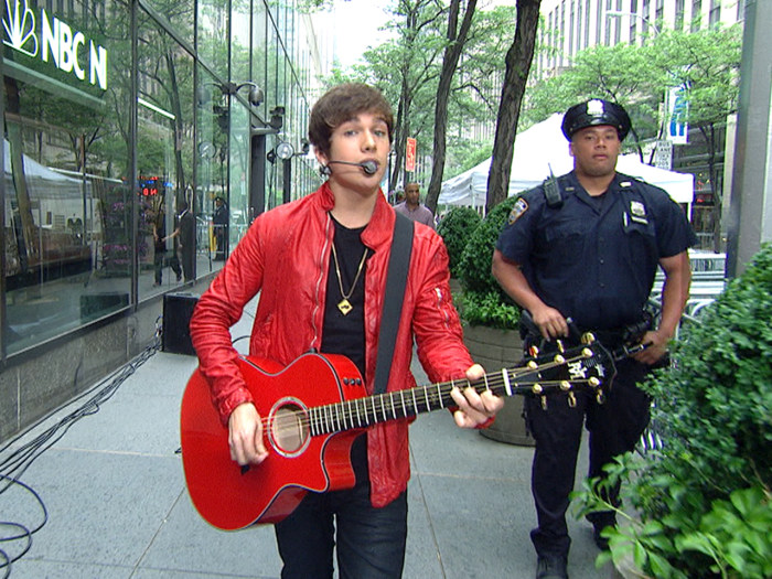 Mahone strolls casually from Studio 1A to the plaza while playing.