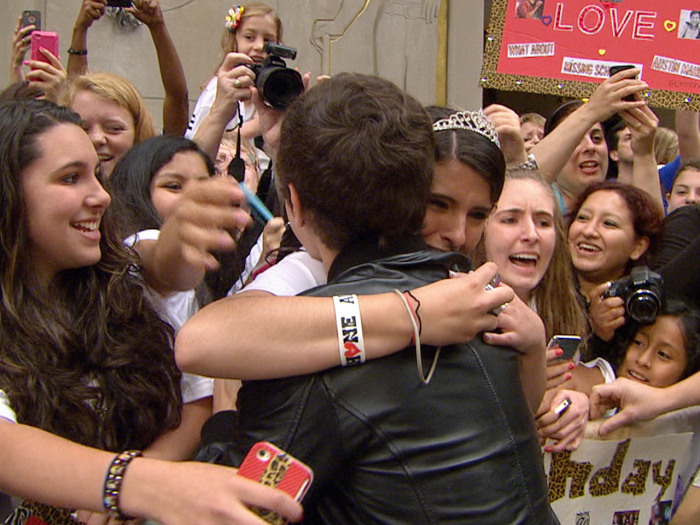 A girl in a tiara hugs Mahone on the plaza.