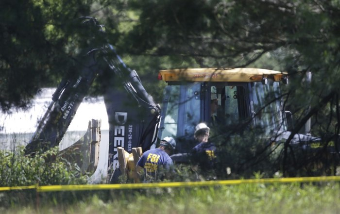 Members of an FBI evidence response team look over an area being cleared in Oakland Township, Mich., Tuesday, June 18, 2013 where officials continue t...