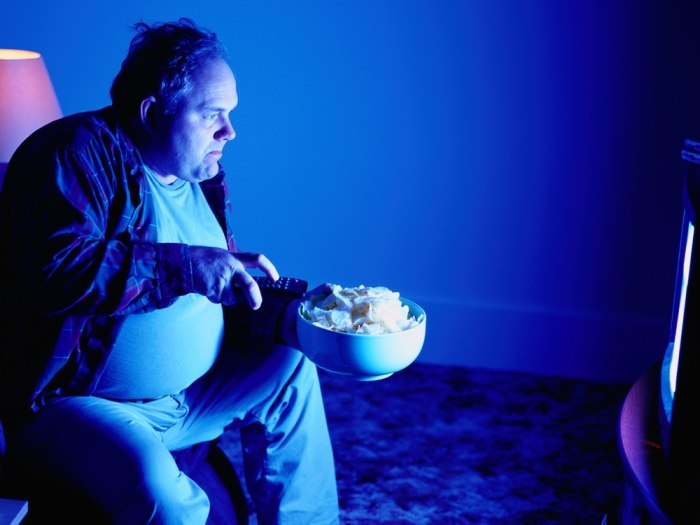A man eats potato chips while watching TV.