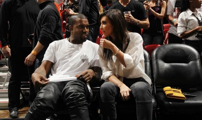 MIAMI, FL - DECEMBER 6: Recording Artist Kanye West and Reality Star Kim Kardashian talk prior to the New York Knicks , Miami Heat game on December 6,...