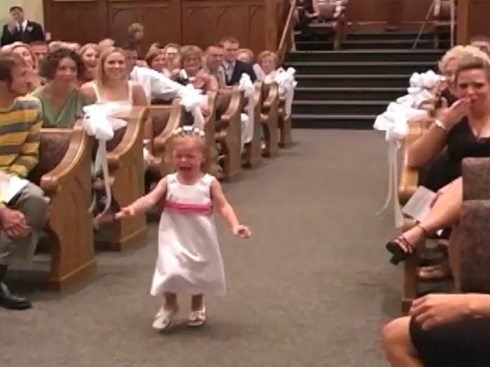 Not having much fun: One little flower girl was showing crying down the aisle in a new YouTube video.