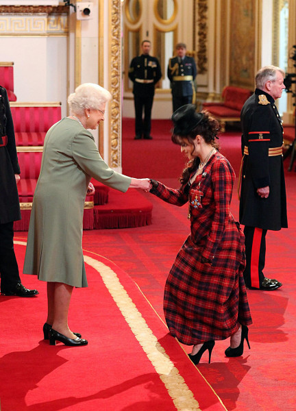Queen Elizabeth II presents Helena Bonham Carter with a medal at Buckingham Palace on February 22, 2012.