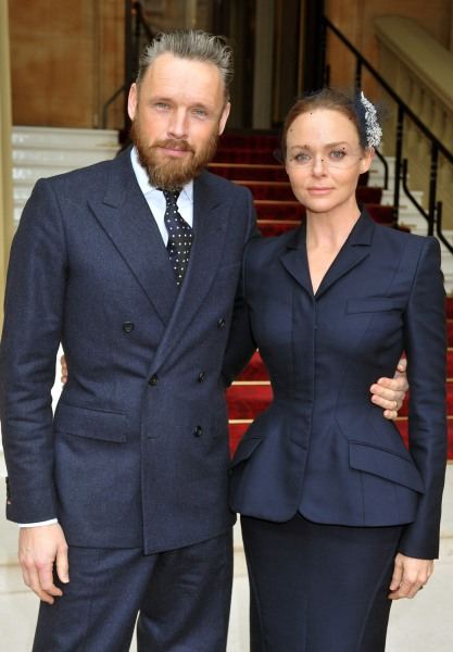 Alasdhair Willis with his wife Stella McCartney pose at Buckingham Palace.