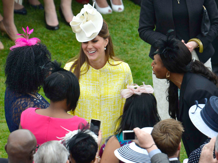 Duchess Kate talks to guests as she attends a Garden Party in the grounds of Buckingham Palace hosted by Queen Elizabeth II on May 22, 2013.