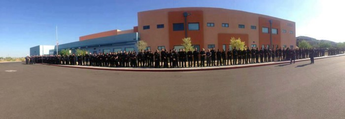 Phoenix police department officers line a school sidewalk as they wait for the arrival of 5-year-old Tatum Raetz, whose father was killed in the line of duty three days before her kindergarten graduation.