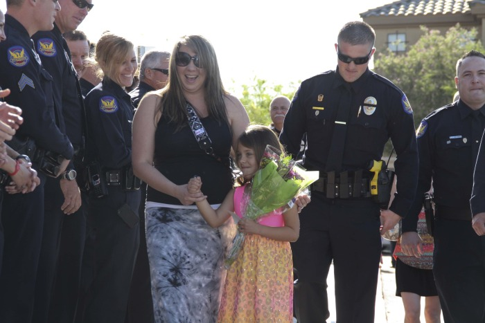 Stephanie Raetz and her 5-year-old daughter, Tatum, walk along a line of Phoenix police officers attending the girl's kindergarden graduation. Tatum's father was killed in the line of duty three days earlier.