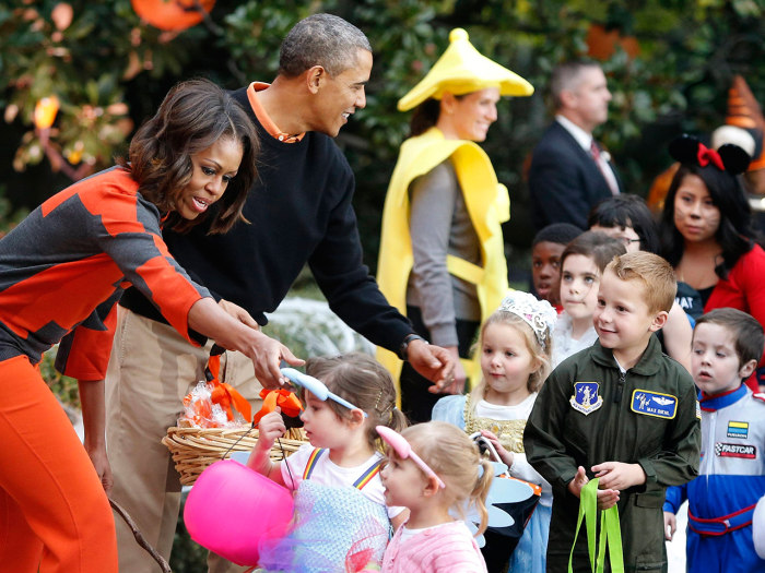 U.S. President Barack Obama (2nd L) and first lady Michelle Obama (L) give Halloween treats to visiting children at the White House in Washington, Oct...