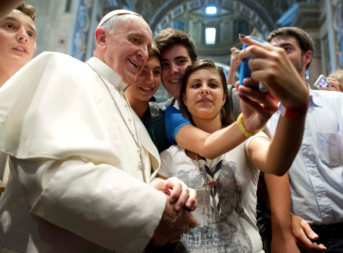 Pope Francis poses with youths during a meeting with the Piacenza diocese in Saint Peter's Basilica at the Vatican in this August 28, 2013 picture pro...