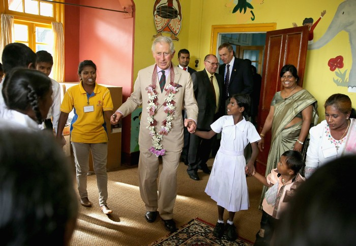 NUWARA ELIYA, SRI LANKA - NOVEMBER 16:  Prince Charles, Prince of Wales takes part in the 'Hokey Cokey' with disabled children as he visits MEDCAFEP D...
