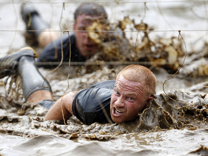 Competitors swim through mud underneath electrified wires on July 15, 2012, during the Tough Mudder at Mt. Snow in West Dover, Vt. The Tough Mudder is a nine-mile endurance event in which competitors run through a military-style obstacle course complete with mud, water and fire.