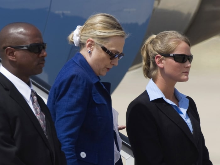 U.S. Secretary of State Hillary Clinton steps down between Secret Service officers upon arriving at Torrejon's air base, near Madrid, July 1, 2011. Cl...