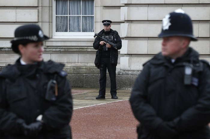 Image: British police officers guard the grounds of Buckingham Palace in London on Monday after a man armed with a knife tried to dart through a palace gate.