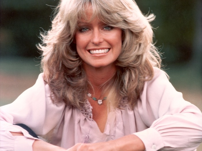 1975: (FILE PHOTO) Publicity portrait of American actor and model Farrah Fawcett smiling while sitting outdoors in blue jeans and a mauve blouse. Fawc...