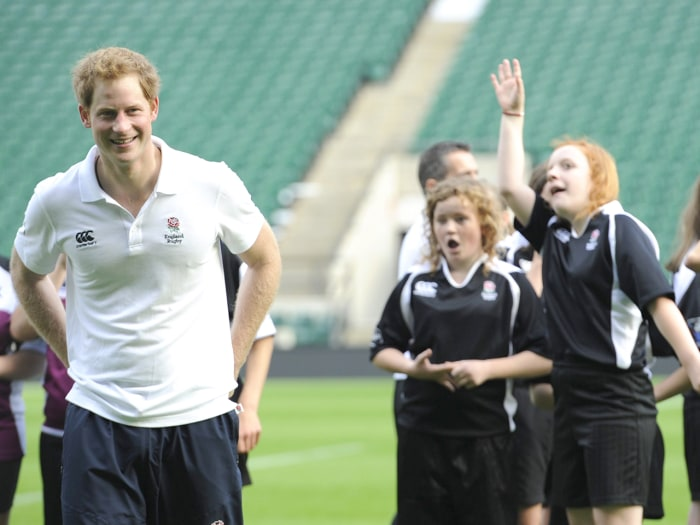 Image: Prince Harry playing football with school children