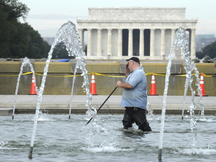 With the Lincoln Memorial in the distance, a worker cleans the fountain at the World War II Memorial in Washington, Thursday, Oct. 17, 2013. Barriers ...