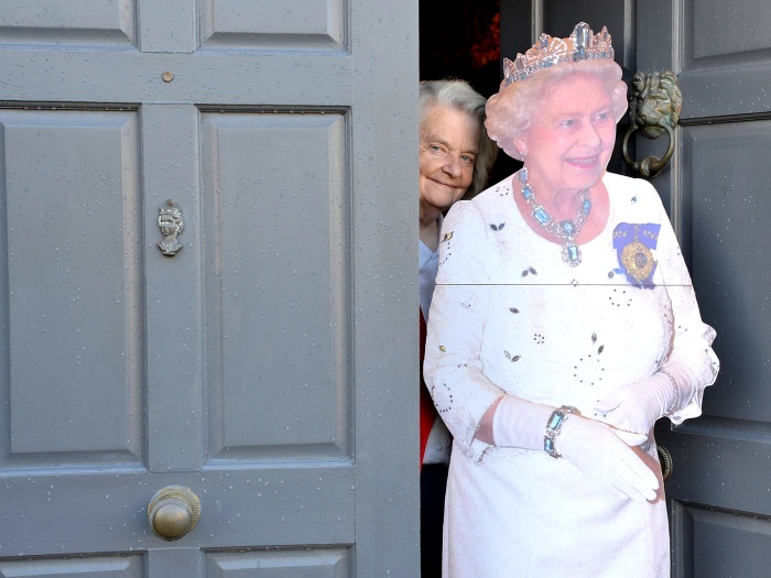 Image: Margaret Tyler poses next to a cutout of a life-size figure of Britain's Queen Elizabeth  II at the front door of her house in London.