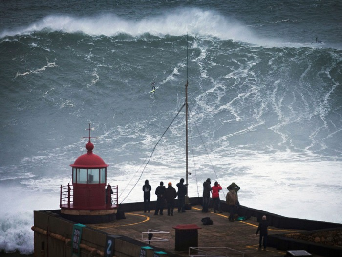 People watch an unidentified surfer ride a big wave at the Praia do Norte, north beach, at the fishing village of Nazare in Portugal's Atlantic coast ...