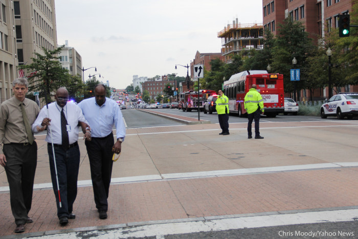 Navy Yard employee Omar Grant, right, leads a blind colleague to safety after  the deadly shooting at the Navy Yard in Washington, D.C, on Sept. 16.