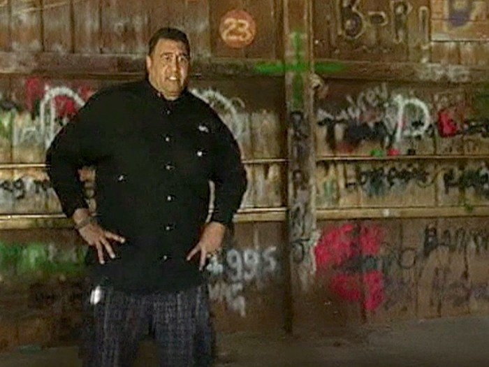Holloway stands behind a graffiti-stained wall left behind by some of the people who broke into his home and held a Labor Day Weekend party.