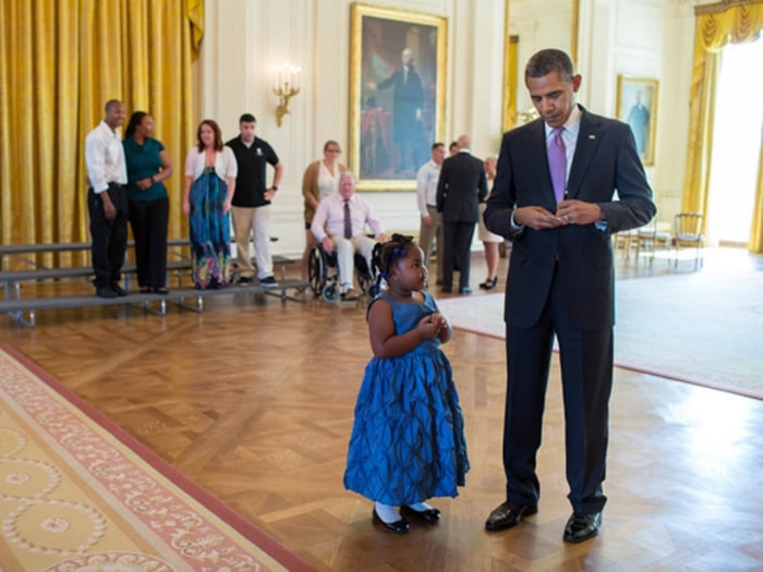 President Barack Obama writes a school excuse note for Alanah Poullard, 5, while visiting with Wounded Warriors and their families in the East Room du...