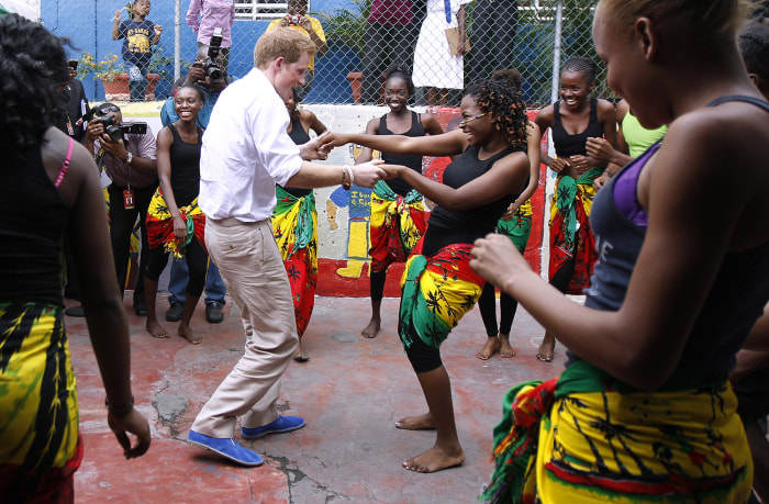 Britain's Prince Harry (L) dances with Chantol Dormer at a youth community center in Kingston, Jamaica March 6, 2012. The Prince is on a week-long tou...