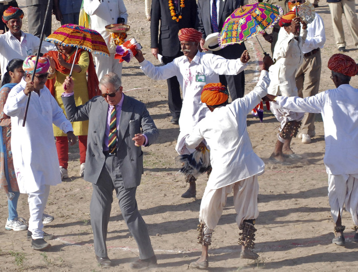 Britain's Prince Charles dances with villagers at Tolasar village near Jodhpur in India's state of Rajasthan October 5, 2010.  REUTERS/Sunil Verma (IN...