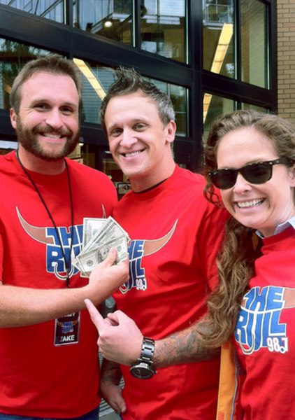 Oregon's KUPL morning show hosts Jake Byron, Howie Drumond and Monica Lunsford show off cash they plan to hide in groceries throughout the Pacific Northwest.