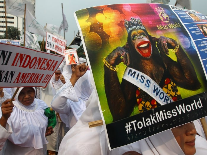 In this Friday, Sept. 6, 2013 photo, Muslim women hold posters reading: Indonesia is not America, left, and Reject Miss World, during a protest demanding the cancellation of the Miss World pageant, in Jakarta, Indonesia.