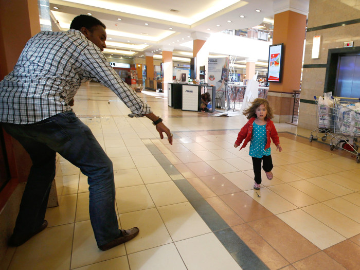 A child runs to safety as armed police hunt gunmen who went on a shooting spree at Westgate shopping centre in Nairobi September 21, 2013. The gunmen ...