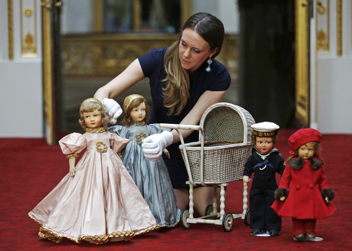 Exhibition curator Anna Reynolds poses with dolls and a wicker toy pram belonging to Britain's Queen Elizabeth and her sister Princess Margaret, at Bu...