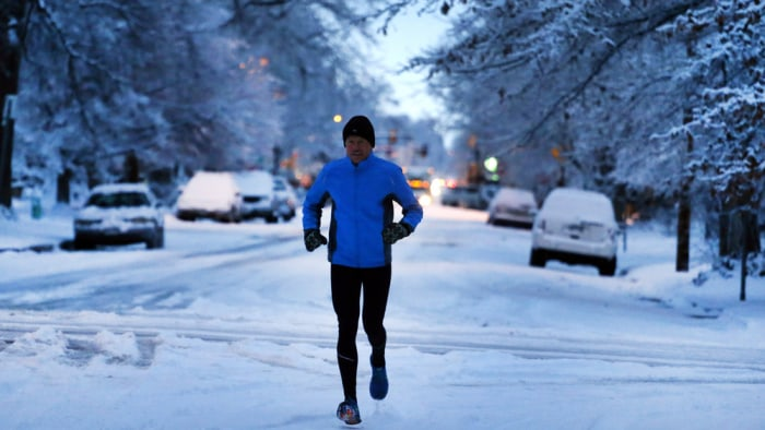Image: A man jogs on a street freshly covered in snow on Jan. 31, 2014, in Boulder, Colo.