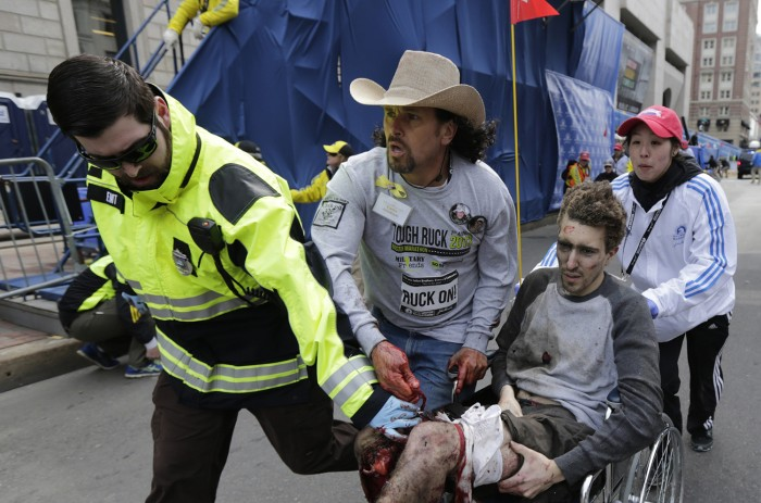 An emergency responder and volunteers, including Carlos Arredondo in the cowboy hat, push Jeff Bauman in a wheel chair after he was injured in an expl...